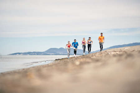 Group of young friends running and exercising on the beach  together.
