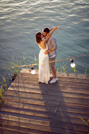 Young   couple the river at sunset kissing.Lifestyle, love, dating, vacation