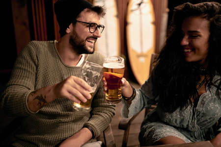 Smiling man and woman enjoying at evening fun and drinks beer together .Couple enjoying drinks together.