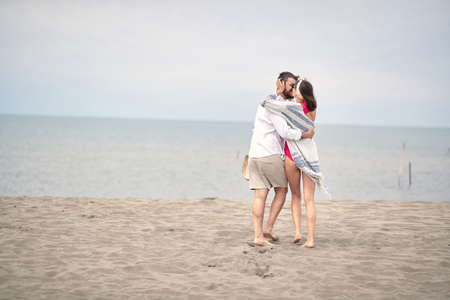 Young romantic couple is kissing and enjoying on the beach. Фото со стока