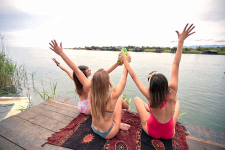 Young  smiling women in swimsuit have fun on the dock on lake and drink beer.