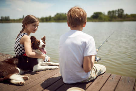 Brother and sister enjoying fishing on the dock of the lake with their dog Standard-Bild