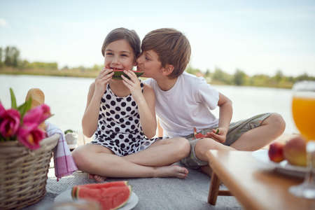 Brother and sister in an emotional moment on a picnic on the dock of the lake