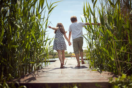 Brother and sister barefoot walking on the dock of the lake