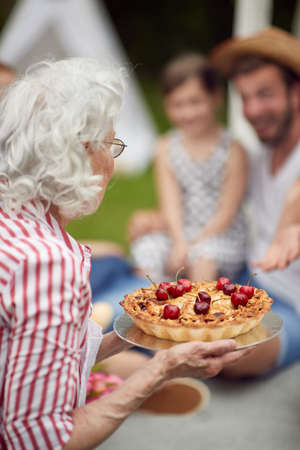 Grandmother prepared cake for a family picnic on a beautiful day