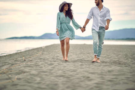 Romantic walk by the sea. Young couple in love having romantic tender moments on the beach.
