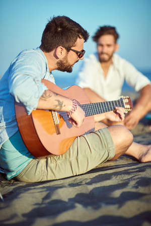 Guys hanging out and playing guitar on the beach Фото со стока