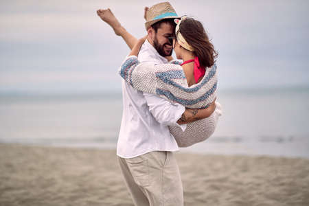 caucasian beardy guy carrying  his girlfriend in his arms at the beach