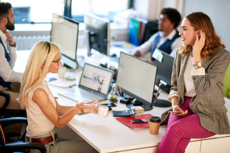 Young women talking to each other in the office Фото со стока