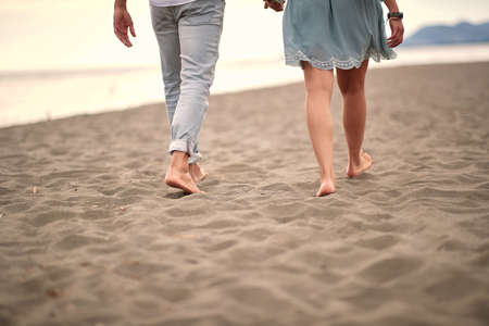 cropped image of  young caucasian couple in casual barefoot walk on sandy beach Фото со стока