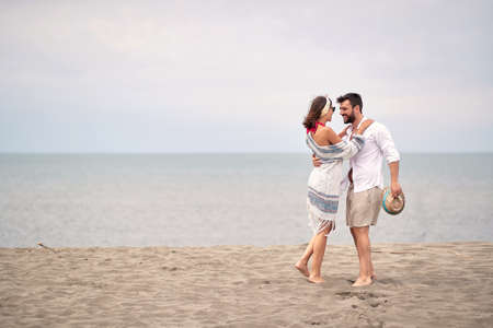 young adult caucasian couple hugging, looking each other, standing barefoot at sandy beach