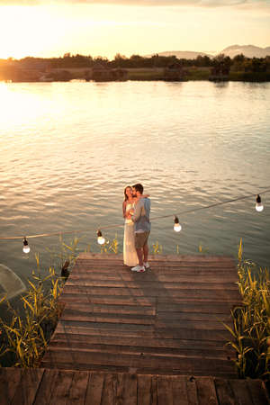 young caucasian couple standing hugged on wooden platform by the lake, cuddling