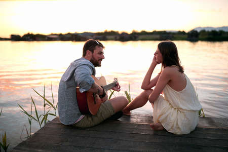 gorgeous caucasian female enjoying in company of a beardy male playing guitar by the lake at sunset