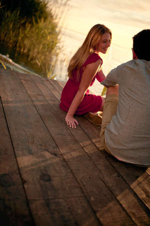 caucasian man and woman sitting on the wooden platform at sunset by the river, enjoying