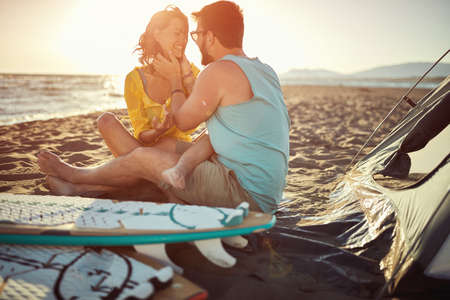 Young attractive surfing couple sitting together on the beach