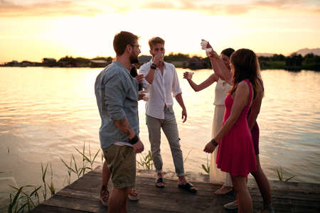 group of young adult people having drink by the river