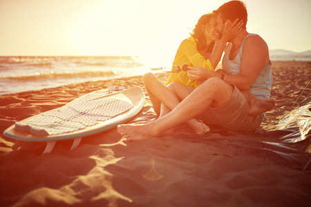 Young attractive surfing couple kissing on the beach
