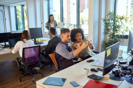 Young colleagues discussing and consulting in the office