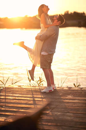 caucasian beardy guy hugging, lifting up his girlfriend at sunset by the river