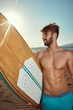 Attractive surfer posing on the beach with surfboard