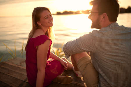 young adult beautiful caucasian couple sitting by the lake, looking each other, talking, Фото со стока