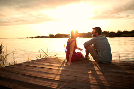 young beautiful caucasian couple sitting on wooden platform by the lake, looking each other, talking at sunset