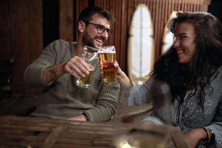 young caucasian couple toasting with glasses of beer Фото со стока