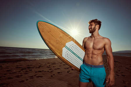 Sexy surfer posing on the beach with surfboard