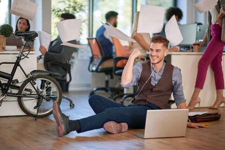 Young man is happy for having successful idea in the office