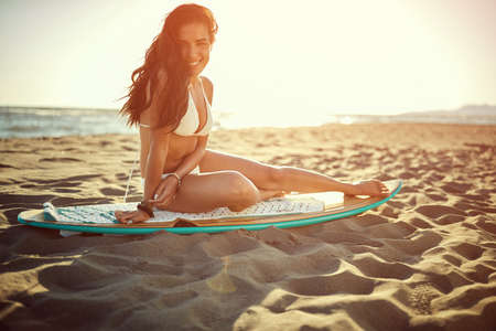 Attractive brunette surf girl posing on the beach with surfboard