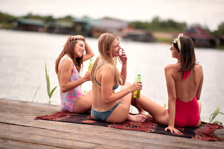 three caucasian female friends having fun by the lake, drinking beer, laughing Фото со стока