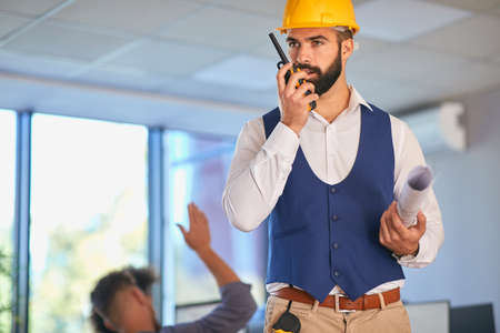 Young architect using walkie talkie from the office