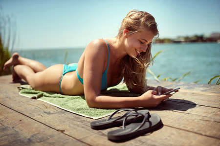 Young woman sunbathing at the dock while on vacation