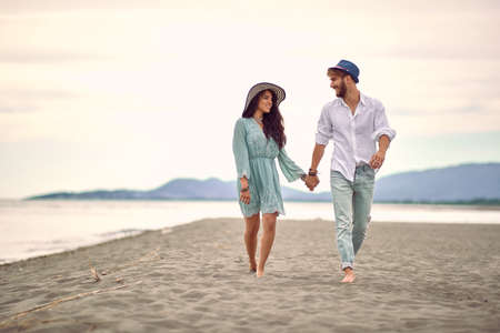young adult caucasian couple in love walking on beach, holding hands