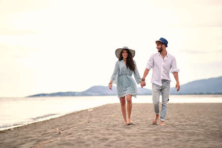 young adult couple in love walking barefoot, on sandy beach, holding hands