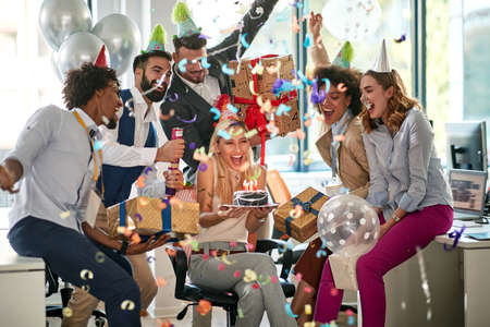 Young caucasian businesswoman surprised by her colleagues for her birthday at work in office.