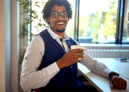 Young african american employee having a coffe break in the office