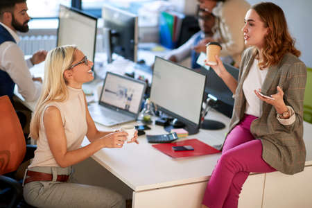Young women talking to each other in the office on a brake