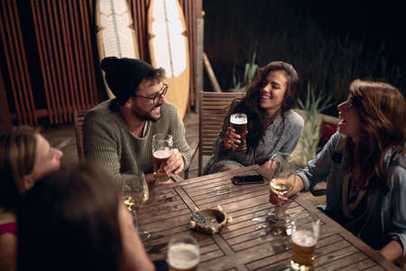young adult caucasian friends socializing, drinking beer and wine, talking, laughing, joking
