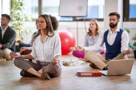 Young colleagues relaxing and having yoga in the office