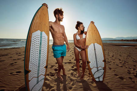 Young attractive surfing couple posing together on the beach