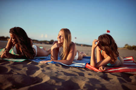 Three girlfriends tanning and relaxing on the beach