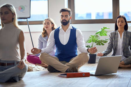 Young colleagues having yoga and focusing in the office