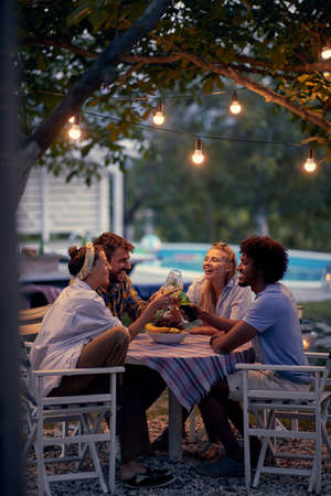 Young smiling people party at picnic after sunset.