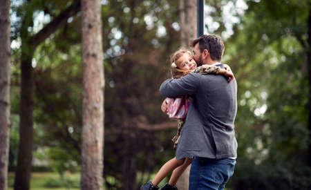 Dad embracing daughter after school in park