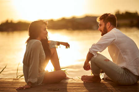 Young couple in emotional chatting on the sunset on the shore of the lake