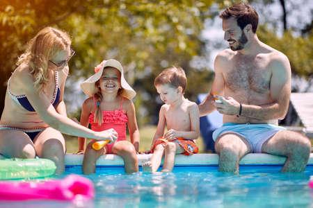 Sun protection - Family put suncream on little smiling children before swimming.