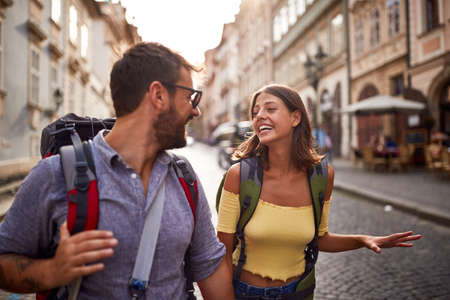 Young boyfriend and girlfriend traveling together smiling and enjoying at summer vacation. Фото со стока