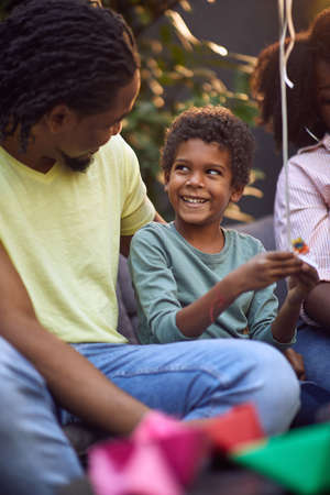 young afro-american boy talking with his father, looking at him, smiling,