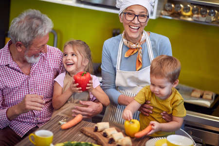 top view of grandparents enjoying with their grandchildren in the kitchen, laughing